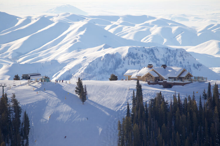 the small town of sun valley idaho blanketed in snow in the middle of winter, with a ski resort and lots of evergreen trees next to a ski run