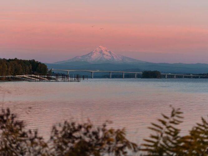 the small town of vancouver washington with mt hood in the background at sunset wtih a bridge spanning the columbia river