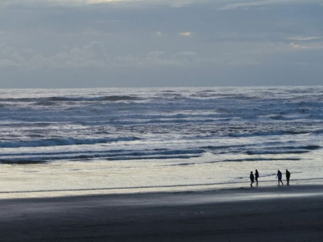 four people standing on the beach in the afternoon light