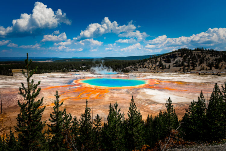 Bright blue geyser ringed with orange iron deposits, seen from above at Grand Prismatic Spring in Yellowstone, a great Idaho weekend getaway